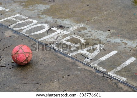 old red ball in wet field at small village