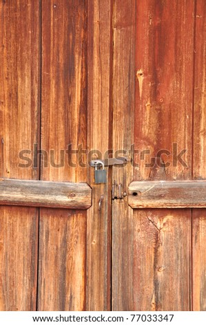 Old red barn door with a lock. - stock photo