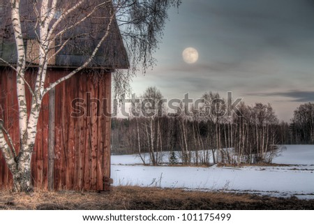 Old red barn in a countryside landscape with full moon - stock photo
