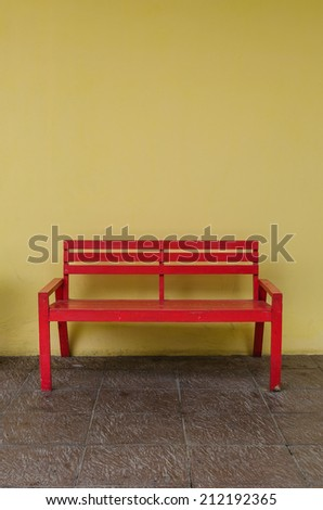 Old red bench on dirty floor and yellow wall - stock photo