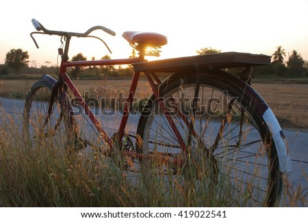 Old red bicycle parked on roadside with dry meadows in evening sunlight