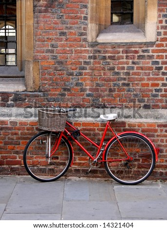 Old red bike with basket in Cambridge - stock photo