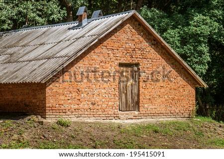 Old red brick barn in remote village. - stock photo
