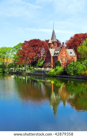 Old red brick castle and green trees reflected in water under blue sky - stock photo