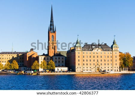 Old red brick church on blue water under blue sky