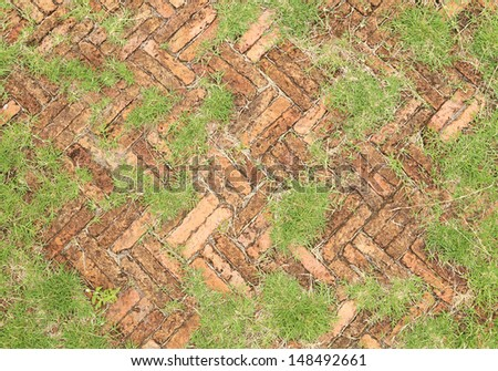old red brick paving stones with grass growing along (for textural background) - stock photo