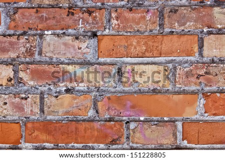 old red brick wall with graffiti signatures   - stock photo