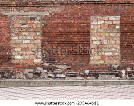 Old red brick wall with two bricked up windows.