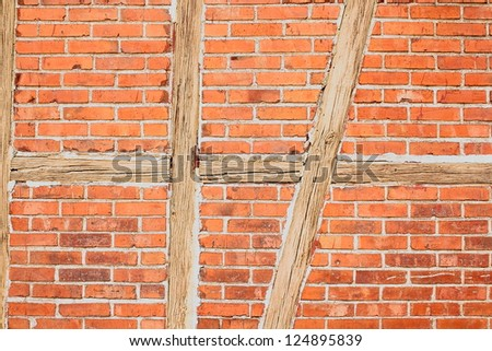 Old red brick wall with wooden beams as background closeup