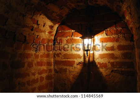 Old red bricks wall and light hanging on the wall. Kremlin in Kolomna, Moscow region, Russia. - stock photo