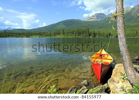 Old red canoe adhered to a tree on fine lake in an environment of mountains (Jasper National Park, Alberta, Canada)