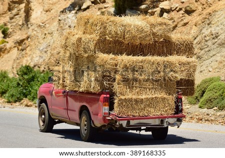 Old Red Car transporting a huge  load of Hay - stock photo