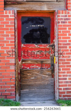 Old red door entrance to abandoned building - stock photo