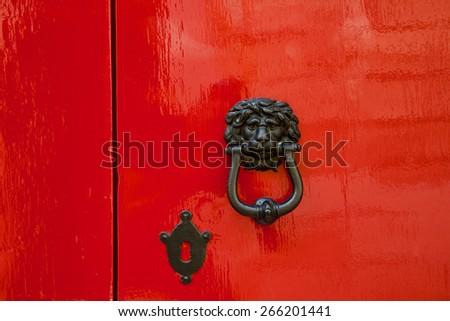 Old red door with lion head metal knockers, Mdina, Malta.  - stock photo