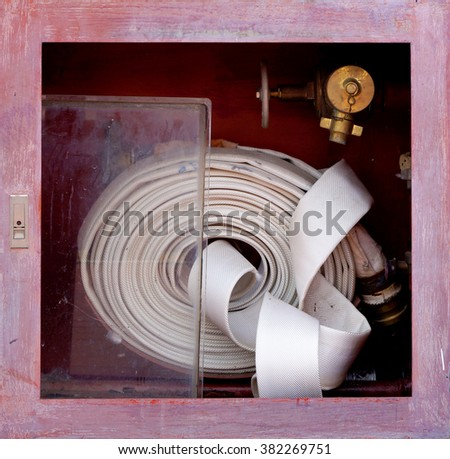 Old red fire hose - stock photo