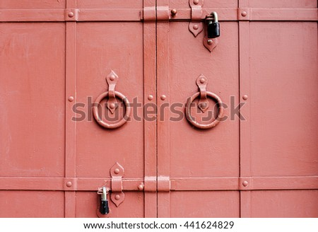 Old red gate doors with locks, closeup shot - stock photo
