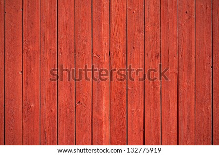 Old, red grunge wood vertical panels on a rustic barn - stock photo