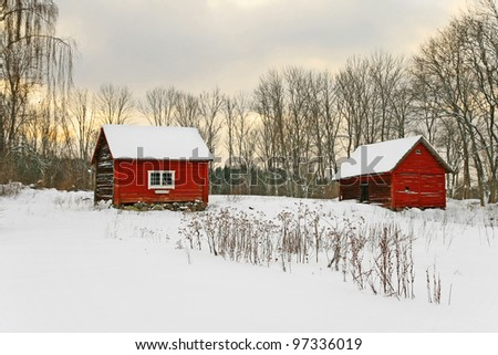 Old red houses in a snowy landscape. Swedish winter. - stock photo