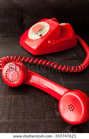 Old red phone handset unhooked from its housing