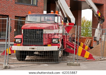 Old red platform lifter truck on construction site - stock photo