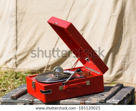 old red portable gramophone on background army tent - stock photo