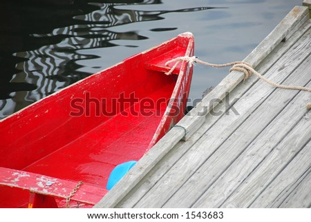Old red row boat tied to a pier in Perkins Cove, Maine - stock photo