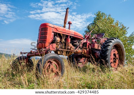 Old red rusty tractor in a field - stock photo