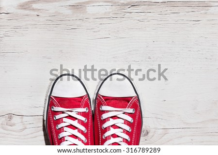 Old red shoes on wooden background - stock photo