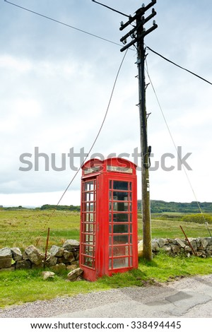 Old red telephone booth with a pole at the coast of the scottish island Mull, copy space - stock photo