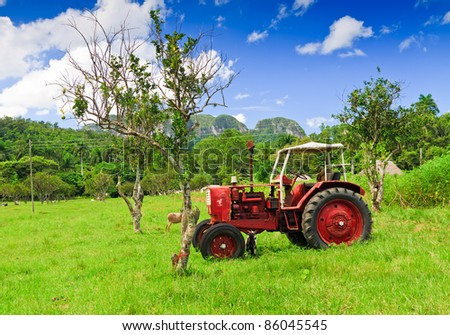 Old red tractor in a green field - stock photo