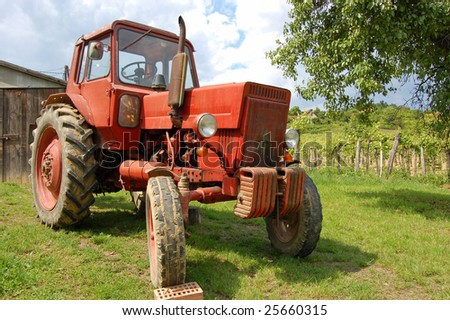 Old red tractor in the vineyard