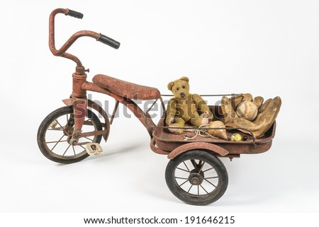 Old red tricycle from childhood Nostalgic vintage toys including my straw Teddy bear  - stock photo