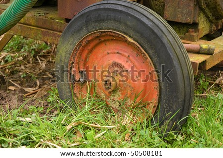 Old red wheel on mobile waterpump - stock photo