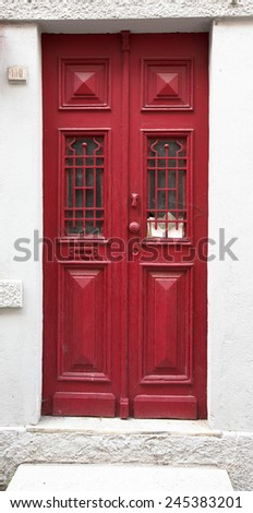 Old red wooden door with window and grid. - stock photo