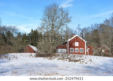 Old red wooden farm house and barns in Sweden under a clear blue sky in winter. - stock photo