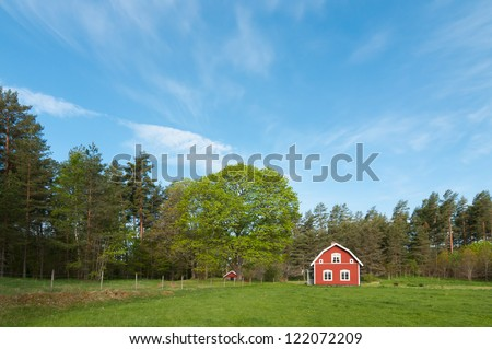 Old red wooden farmhouse in Sweden - stock photo