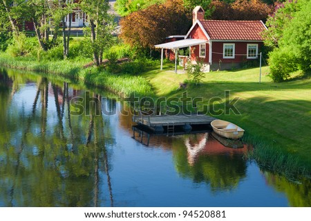 Old red wooden house in the village Hoegsby, Sweden,in the foreground the river Eman. - stock photo