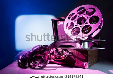 Old reel of film on a suitcase - stock photo