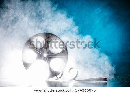 Old reel of film with smoke and back-light - stock photo