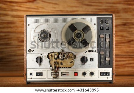 Old reel tape recorder on wooden background - stock photo