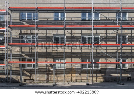 Old residential building renovation site with scaffolding lit by sunlight