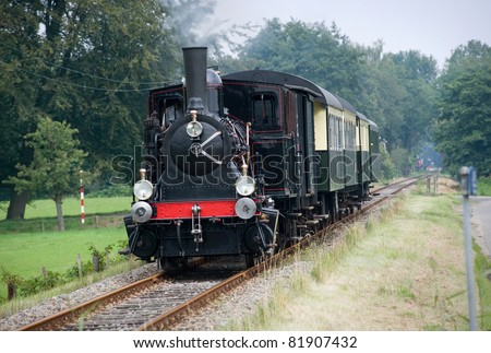 Old restored steam train with wagons still riding for fun with tourists in The Netherlands. - stock photo