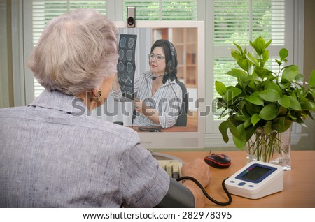 Old retired woman sitting in front of monitor. She has just sent her blood pressure and pulse information to virtual doctor. At the same time, physician is looking at her CT x-ray on the screen - stock photo