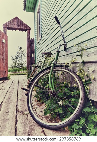 Old retro bike in the house in the village. - stock photo