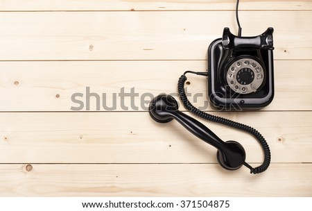 Old retro black phone on wooden board, top view, DOF, focus on phone - stock photo
