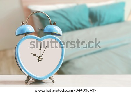 old retro blue clock over bedroom background ,abstract background to time management concept. - stock photo