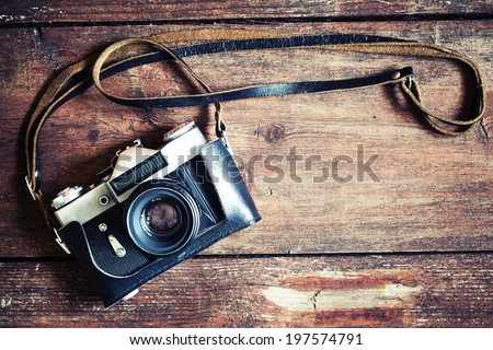 Old retro camera on vintage wooden boards abstract background - stock photo