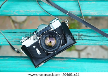 Old retro camera on vintage wooden boards. abstract background - stock photo
