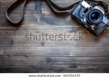 Old retro camera on vintage wooden table background - stock photo