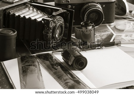 Old retro cameras on a table with photographs, negatives and films with Copy Space./Retro photo cameras on a table